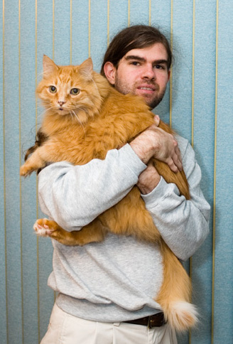 Christopher Crawford holding his gigantic orange Maine Coon Cat.