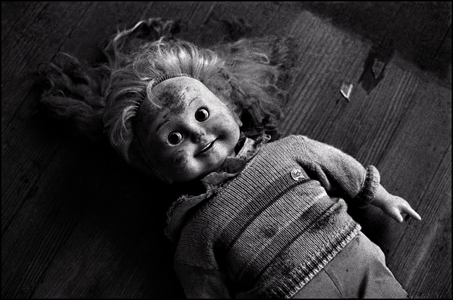 A smiling Cricket Doll on the dusty floor of an abandoned farmhouse.