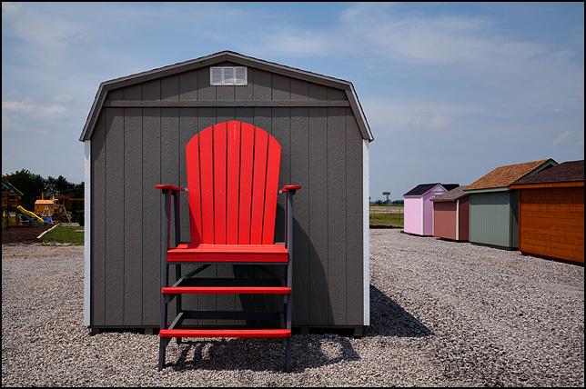 A gigantic red chair in front of a storage shed at an outdoor furniture store.