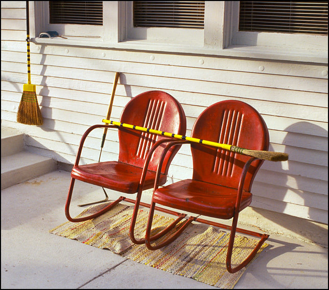 A pair of red motel chairs behind a farmhouse in rural Indiana.