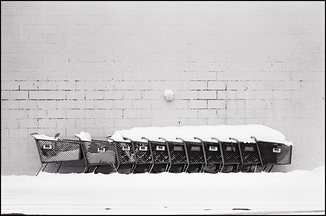 Shopping carts buried in snow next to a big-box store.