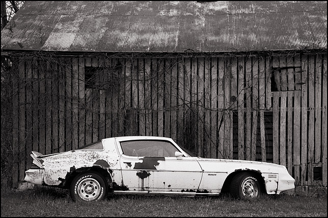 1980 Chevrolet Camaro rusting away beside a weatherbeaten barn in rural Indiana.