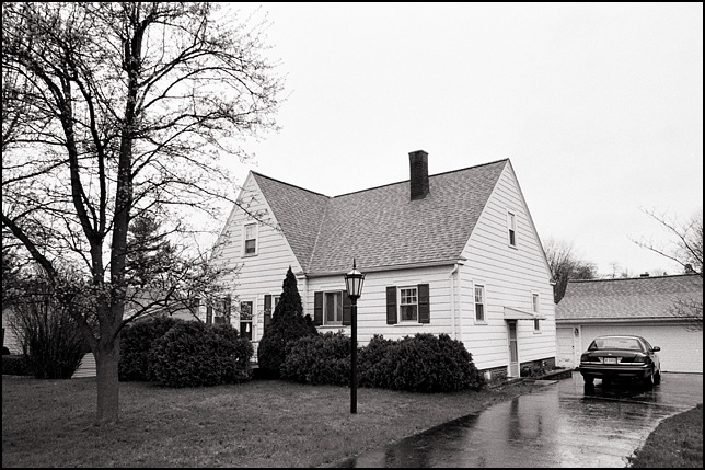 A whote house surrounded by evergreen bushes on a rainy evening.