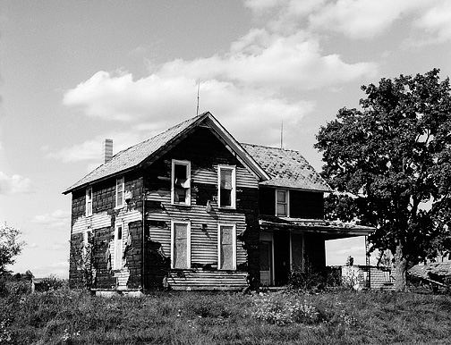 An abandoned farmhouse in Allen County, Indiana near Fort Wayne International Airport. The original siding is visible under tar paper that covered it. There are lightning rods on the roof.