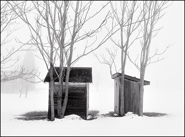 An outhouse and a small shed sit side by side among a group of trees on a farm in southwest Allen County, Indiana. The outhouse and shed are veiled in heavy fog and the ground is covered in snow. A barn is visible through the haze in the background.