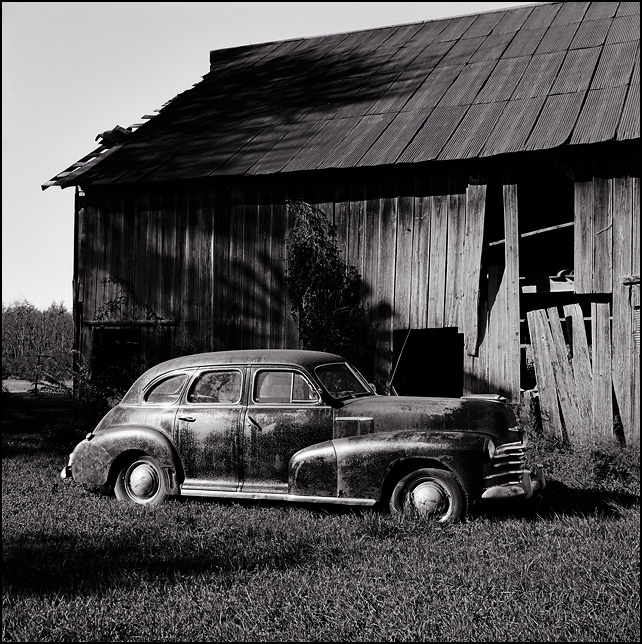 A black 1946 Chevrolet sedan in front of an old barn on a farm in Allen County, Indiana. The shadow of the windmill falls on the barn behind the car.