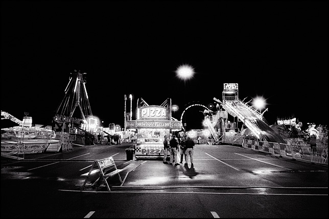 A deserted carnival at night with several sheriff's deputies standing in front of a lit up pizza booth.