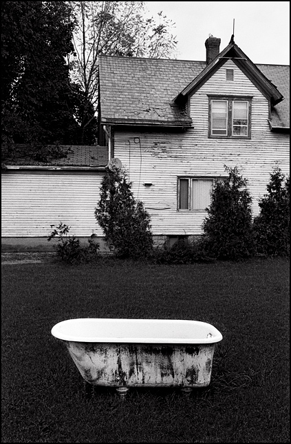 An old cast iron bathtub sits n a yard next to a house that is being renovated on Spy Run Avenue in downtown Fort Wayne, Indiana.