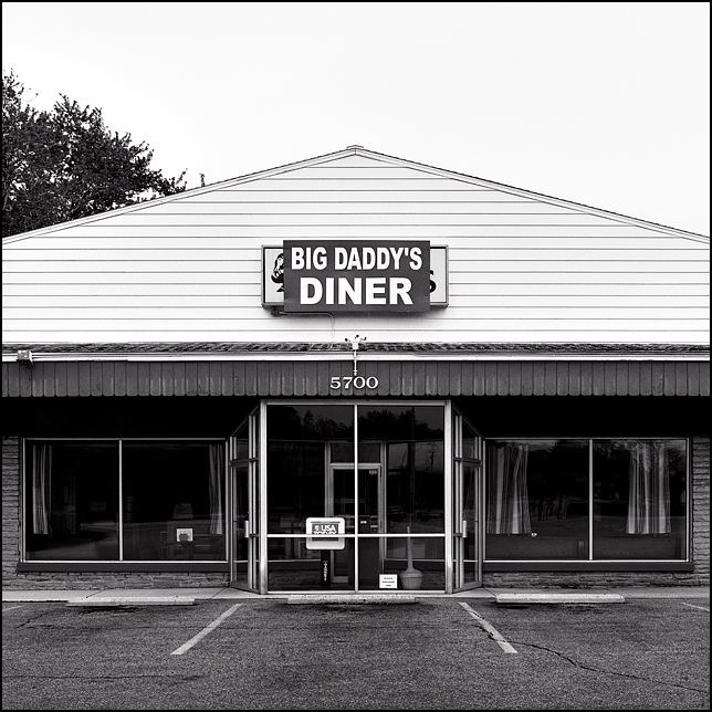 Karen's Kitchens donut shop and restaurant on Blufton Road in the Waynedale area of Fort Wayne, Indiana. The sign is covered by a new sign saying Big Daddy's Diner. A USA Today newspaper machine and a Smoker's Outpost ashtray stand inside the foyer.