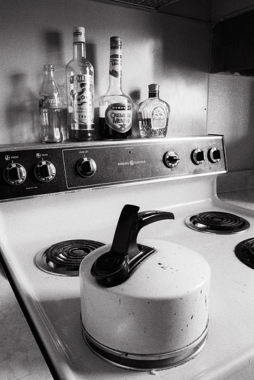 An old enameled tea kettle sits on the stove with half-empty liquor bottles behind it.