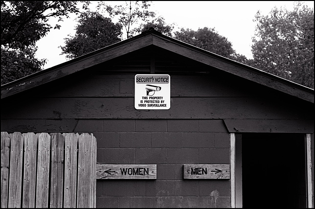 A public restroom in Memorial Park in Lebanon, Indiana. The sign above the entrances shows a video camera and it says that the premises are under video surveillance.