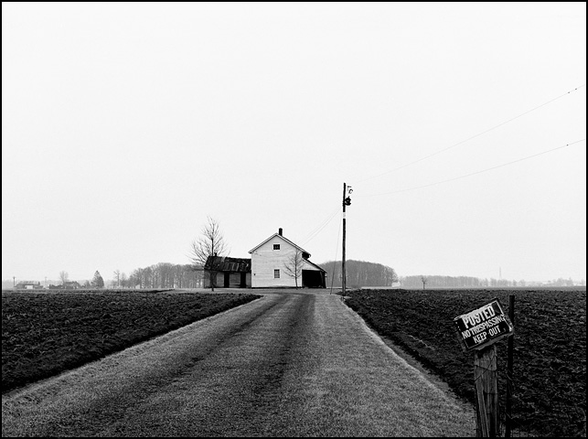 An abandoned farmhouse at the corner of Minnich Road and Monroeville Road near Hoagland, Indiana in Allen County. The house sits in the middle of a plowed field at the end of a long driveway with a no trespassing sign.
