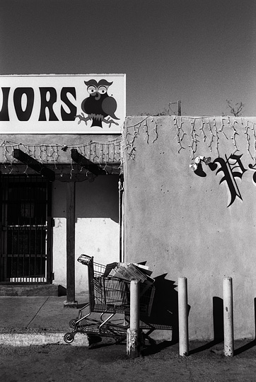 Owl's Liquors on Saint Francis Drive in Santa Fe, New Mexico. The name Paul Pacheco Senior is painted in spanish gothic lettering on the front of the pueblo style adobe building, and a shopping cart full of carboard boxes is wedged behind a cement pedestal in front of the store.