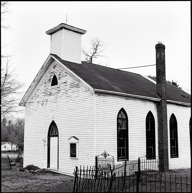 The little white church at the Prairie Grove Cemetery in the Waynedale area of Fort Wayne, Indiana. The chapel is white clapboard with black arched windows and a brick chimney. Wrought iron fence surrounds the cemetery and church.