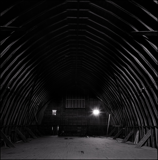 The dark hayloft inside a huge wooden barn at an abandoned dairy farm.