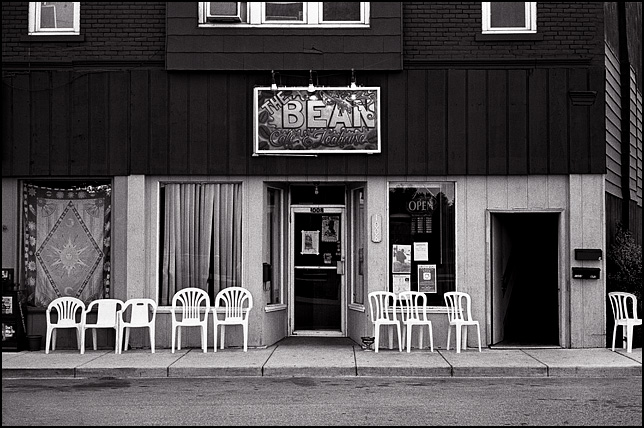 The front of The Bean Coffeeshop on Wells Street in Fort Wayne, Indiana with a row of plastic chairs on the sidewalk flanking the entrance.