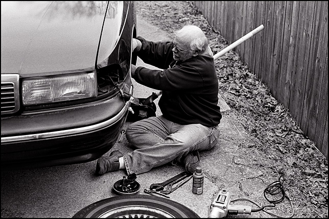 Middle aged man working on a car in the driveway.