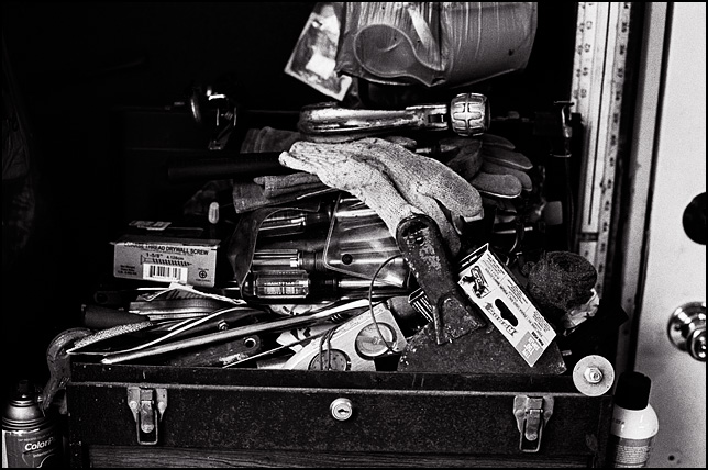 A tool box overflowing with old tools, including gloves, screwdrivers, pipe cutters, screws, a scraper, and a ruler.