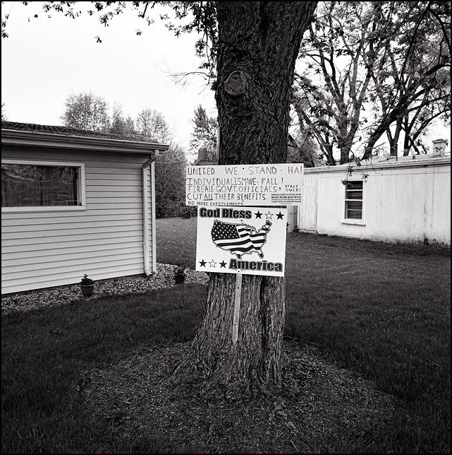 A God bless America sign and an anti-government tea-party militia protest sign nailed to a tree in front of a house in the Waynedale area of Fort Wayne, Indiana.