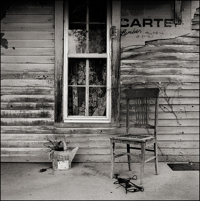 An old wooden chair on the front porch of an abandoned farmhouse.