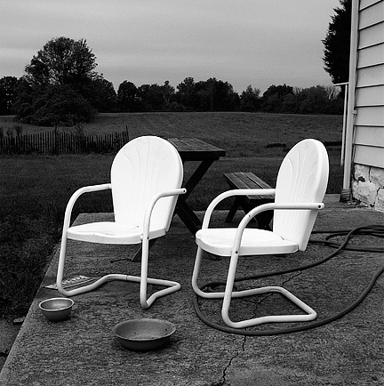 A pair of glowing white metal patio chairs behind a farmhouse at sunset in Allen County, Indiana. Dog food bowls, an old license plate, and a picnic table sit on the patio around the chairs.