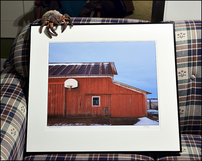 Framed photograph of a red barn with a basketball hoop at dusk by Christopher Crawford.